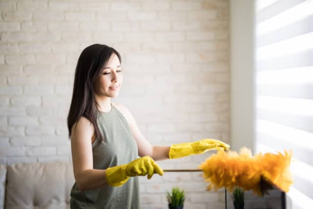 Woman using a swiffer eliminate dust mites.