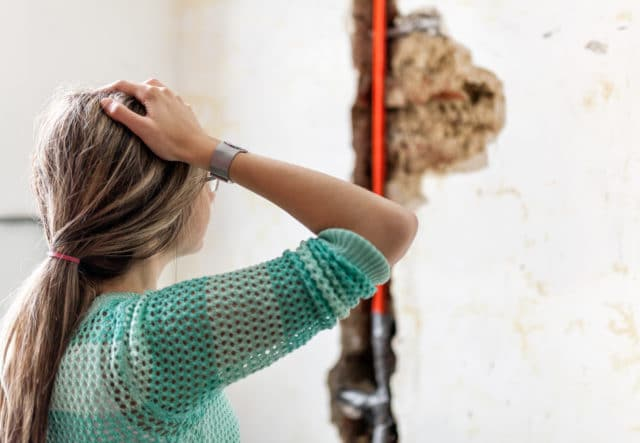 Woman looking at mold and water damage in her home.